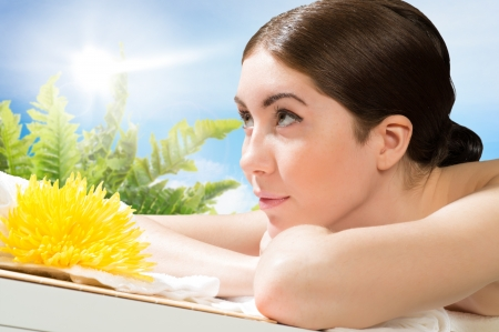 beautiful spa woman lying on the couch, in front of her flower and rolled towel Stock Photo - 20990792
