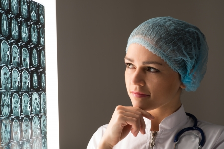 female doctor looking at the x-ray image attached to the glowing screen Stock Photo - 20990806