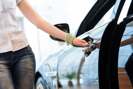 woman opens the door to a new car, car inspection in the showroom Stock Photo