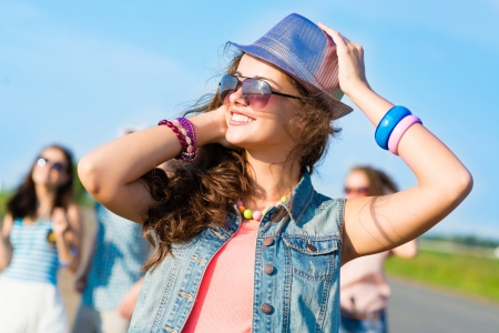 mad girl: stylish young woman in sunglasses on the background of blue sky and friends
