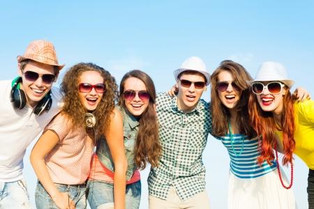 groep jongeren draagt een zonnebril en hoeden knuffelen en staan in een rij, tijd doorbrengen met vrienden Stockfoto