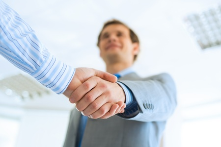 hands joined: young businessman shaking hands with a colleague, an agreement