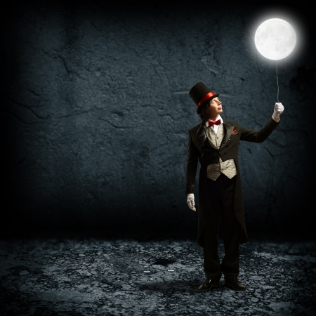 anticipate: magician in top hat and tie, holding a glowing moon on a string Stock Photo