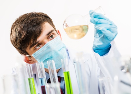 scientist working in the lab, in protective mask, examines a test tube with liquid Stock Photo - 21219551