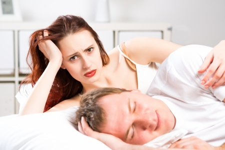 woman sleeping next to her husband in bed, relationship problems people Stok Fotoğraf