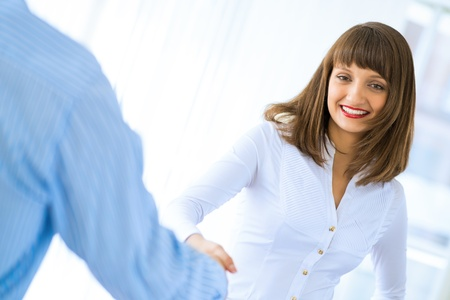 young business woman shaking hands with a client, the agreement between the partners photo