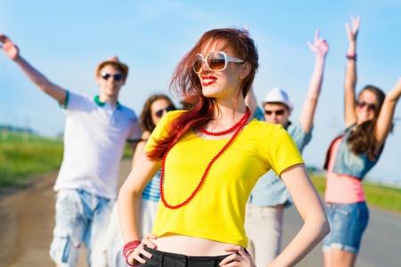 stijlvolle jonge vrouw in zonnebril op de achtergrond van blauwe hemel en vrienden