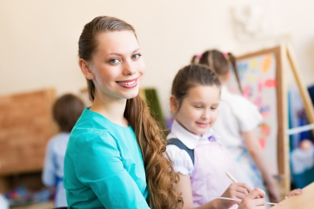 pre adult: children with the teacher engaged in painting at an art school