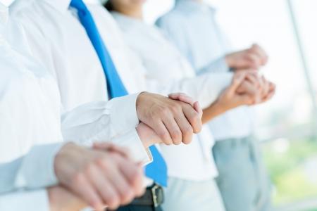 handen van zakenlieden, zakenlieden houden handen, staan in een rij, het concept van teamwork