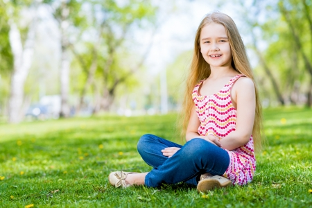 smiling girl sitting in the grass on a summer park photo