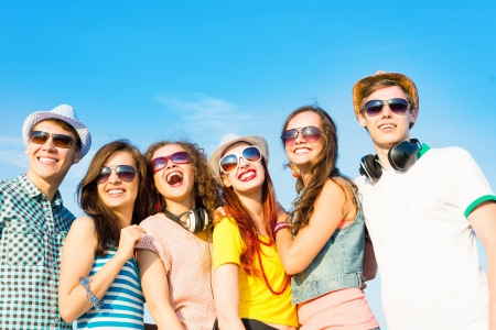 people in a row: group of young people wearing sunglasses and hats hugging and standing in a row, spending time with friends