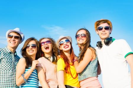 happy young: grupo de j�venes con gafas de sol y sombreros de abrazos y de pie en una fila, pasando tiempo con amigos