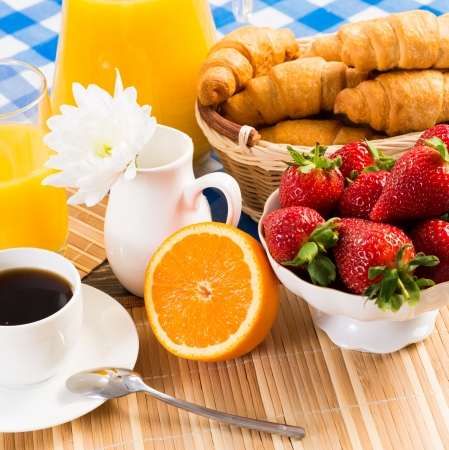 continental breakfast  coffee, strawberry, croissant and juice photo