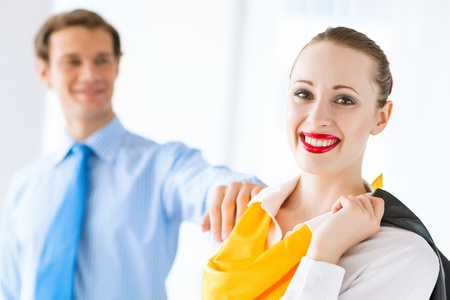 young successful business woman smiling, a colleague put his hand on her shoulder