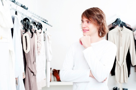 man in shop of clothes, smiles and is happy with purchases photo
