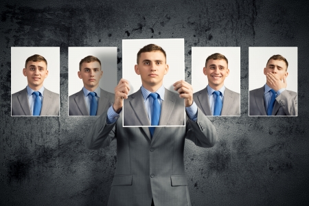 young man holds up a photograph hanging on the wall behind the additional photos with different emotions Stock Photo - 21355408