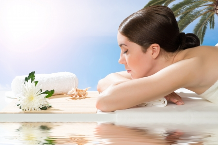 beautiful spa woman lying on the couch, in front of her flower and rolled towel Stock Photo - 21511683
