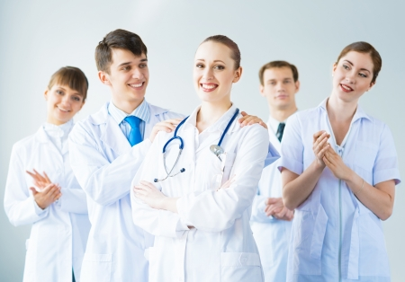 successful doctor, accepts congratulations from colleagues, stand behind him and clap Stock Photo - 21511687