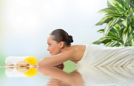 beautiful spa woman lying on the couch, in front of her flower and rolled towel Stock Photo - 21511703