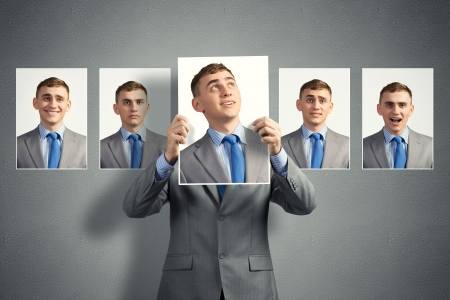 emotional freedom: young man holds up a photograph hanging on the wall behind the additional photos with different emotions Stock Photo