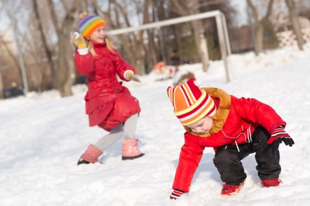 Children in Winter Park playing snowballs, actively spending time outdoors 版權商用圖片