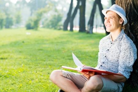 graduacion de universidad: hombre joven que llevaba un sombrero de lectura de un libro en el parque Foto de archivo