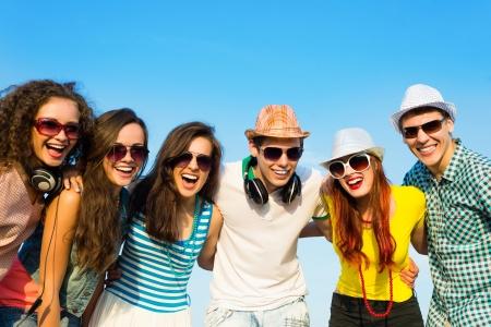groep jongeren die zonnebril en hoeden knuffelen en staan in een rij, tijd doorbrengen met vrienden