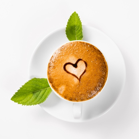 large cup of coffee with heart pattern on the foam and green leaf of mint photo