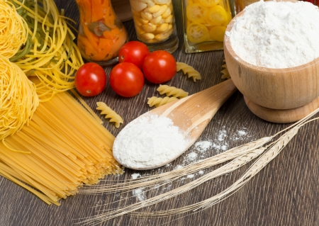 pasta, tomatoes and flour on the spoon, still life photo