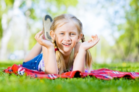 girl in a summer park lies on the rug on the grass photo