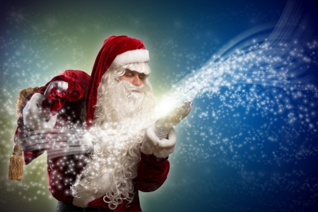 santa claus blows with hands magic sparks holds on shoulder bag with Christmas presents photo