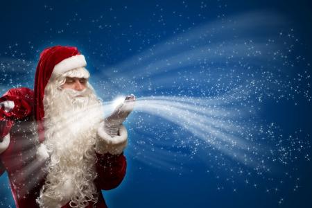 kerstman klappen met de handen magische vonken houdt op schoudertas met kerstcadeautjes Stockfoto