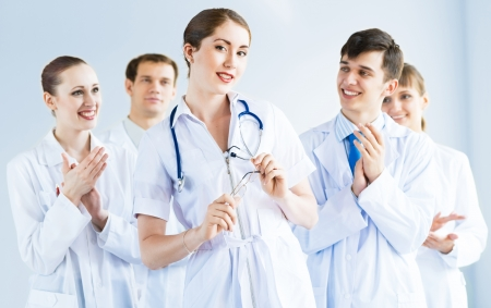 successful doctor, accepts congratulations from colleagues, stand behind him and clap photo