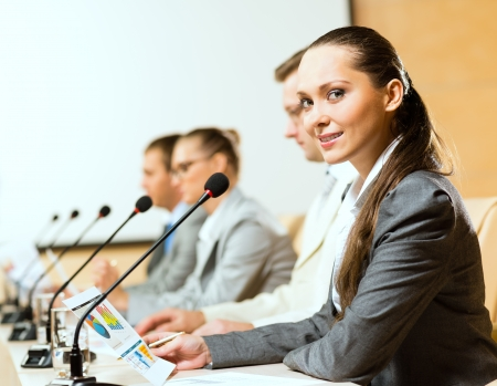 group of business people sitting at the tables at the presentation, woman looking at the camera photo