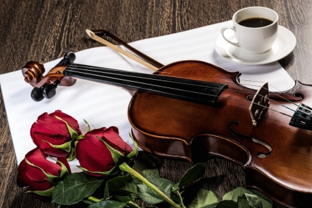 Violin, roses, cup of coffee and music books photo