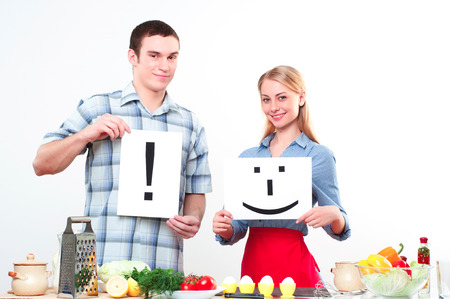 couple holding a plate with signs smile and exclamation photo