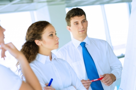 business consultant discussing with colleagues around the flipchart, teamwork Stock Photo - 22362080