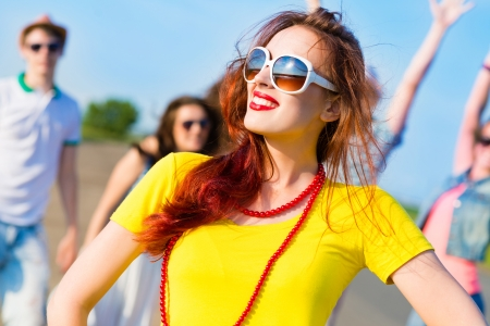 stylish young woman in sunglasses and friends photo
