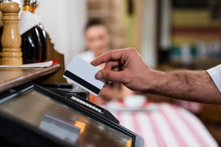 ober voegt de kaart in een computer terminal, tegen een bezoek aan het restaurant