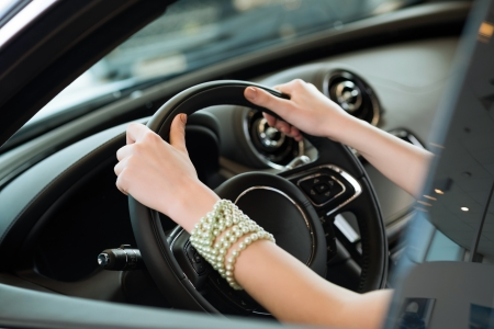 woman s hands holding on to the wheel of a new car in the showroom photo