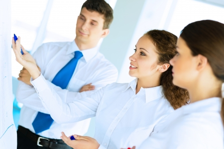 business consultant discussing with colleagues around the flipchart, teamwork Stock Photo - 22767909