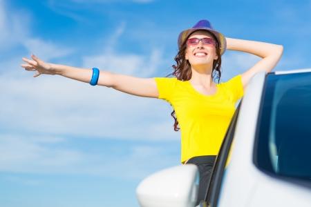 jonge vrouw werd uit de auto-venster, houdt de hand hoed, zwaait met zijn hand en lachen Stockfoto