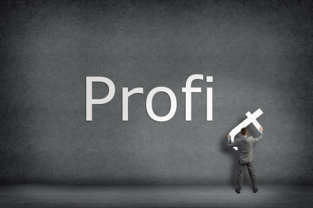 Businessman collects on the wall the word profit, holds the last letter photo