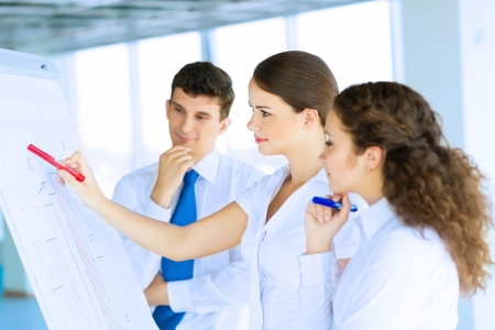 business consultant discussing with colleagues around the flipchart, teamwork Stock Photo - 22767966