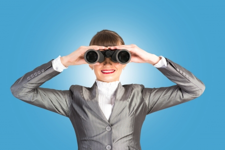 business woman looking through binoculars, looking for a solution to the problem photo