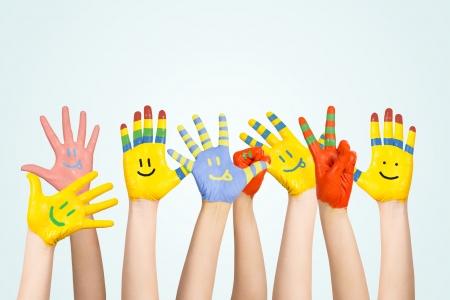 Pintou as mãos das crianças s em cores diferentes com smilies Foto de archivo - 22859065