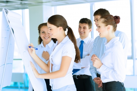 business consultant discussing with colleagues around the flipchart, teamwork Stock Photo - 22919710
