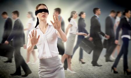 disoriented: young blindfolded woman  seeking a way out in a crowd