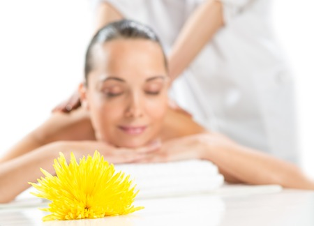 beautiful spa woman lying on the couch, in front of her flower and rolled towel photo