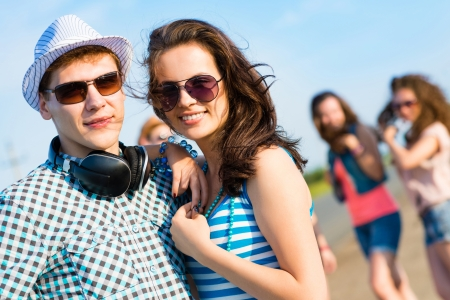 young couple standing on the road, having fun with friends photo